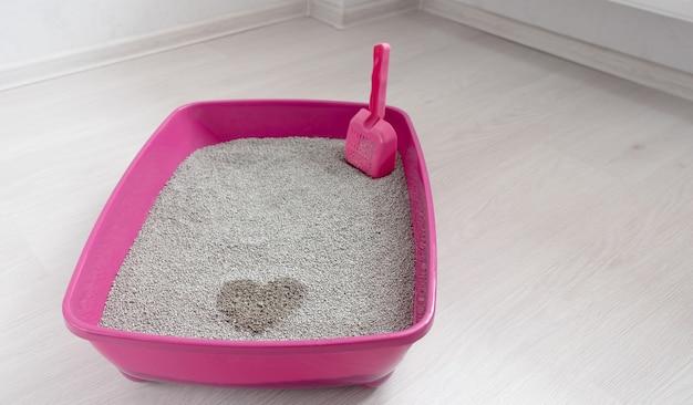 Cassetta igienica per gatti su un lato alto con assorbente di bentonite e paletta nella stanza