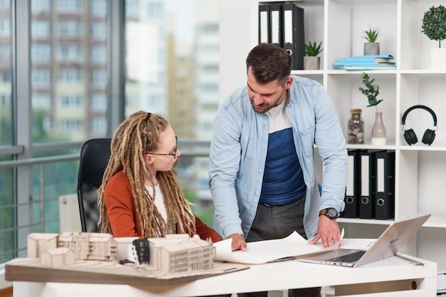 Designer maschili e femminili creativi altamente qualificati e laboriosi che lavorano con modelli di edifici futuri