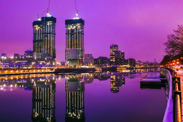 Gli alti grattacieli a mosca si riflettono nell'acqua di notte