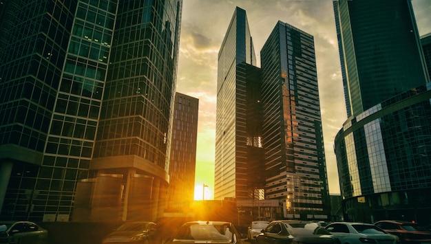 Grattacieli alti al fondo di luce solare di sera