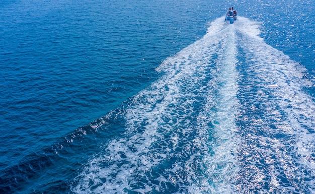Una barca ad alta velocità o uno yacht manovra sulla superficie del mare o dell'oceano. vista aerea.