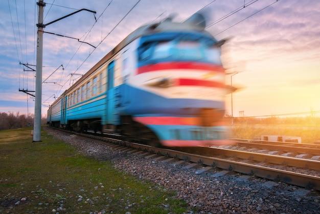 Treno elettrico per passeggeri ad alta velocità in movimento sulla ferrovia al tramonto. vecchio treno pendolare vago stazione ferroviaria contro il cielo blu. viaggi in ferrovia, turismo ferroviario. paesaggio industriale rurale. concetto
