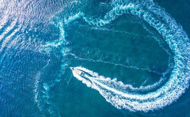 Uno yacht ad alta velocità manovra sulla superficie dell'acqua. vacanze in mare o in mare, noleggio di navi marittime. sport acquatici.