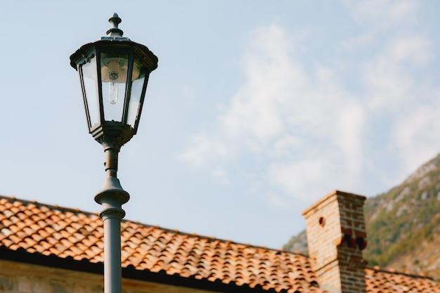 Lampione stradale alto a livello del tetto della casa