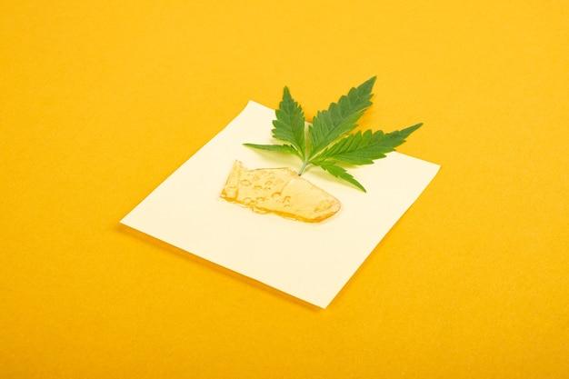 Alto thc, pezzi di cera di cannabis giallo dorato e foglia verde, concentrato di marijuana.