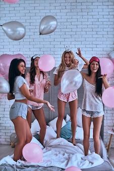 È ora di fare festa! tutta la lunghezza di quattro attraenti giovani donne sorridenti in pigiama impazziscono mentre fanno un pigiama party