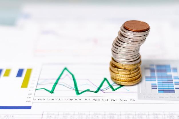 Mucchio di alta vista di monete su diagrammi statistici