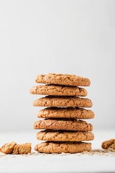 Mucchio di alta vista dei biscotti sul fondo bianco dello spazio della copia