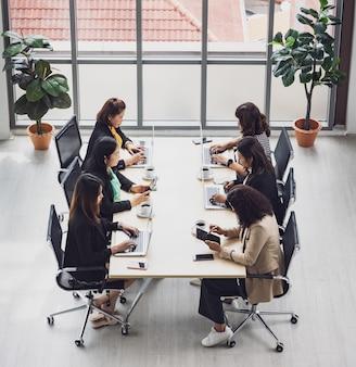 Vista dall'alto di sei donne d'affari dirigenti sedute su ciascuna sedia utilizzando computer portatili e tablet sul tavolo da conferenza in legno nella sala riunioni in ufficio. concetto per incontro di lavoro.
