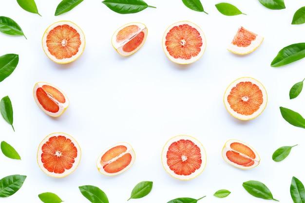 Alta vitamina c. cornice fatta di succose fette di pompelmo su sfondo bianco.