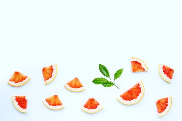 Alta vitamina c. fette di pompelmo succose sulla superficie bianca.