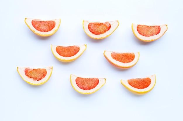 Alta vitamina c. fette di pompelmo succose su bianco.