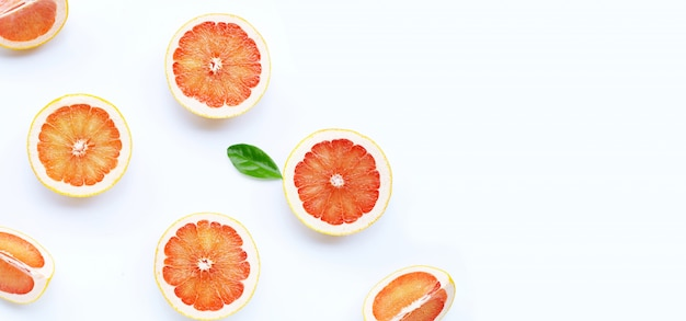 Alta vitamina c. fette di pompelmo succose con foglia su sfondo bianco. copia spazio