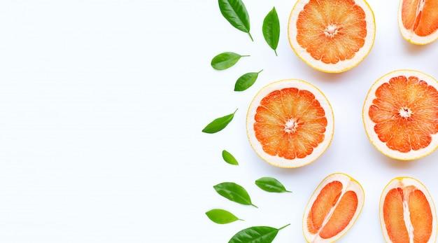 Alta vitamina c. pompelmo succoso con foglie verdi su sfondo bianco.