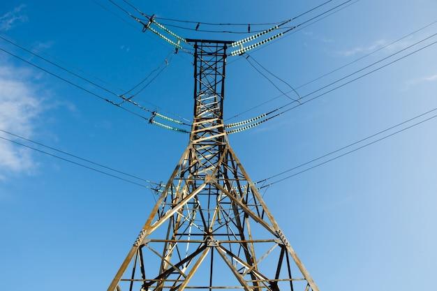 Polo elettrico ad alta tensione e linee di trasmissione serali.