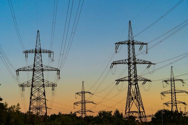 Siluetta della torre elettrica ad alta tensione sull'ora del tramonto, piloni di potenza sullo sfondo del tempo del tramonto