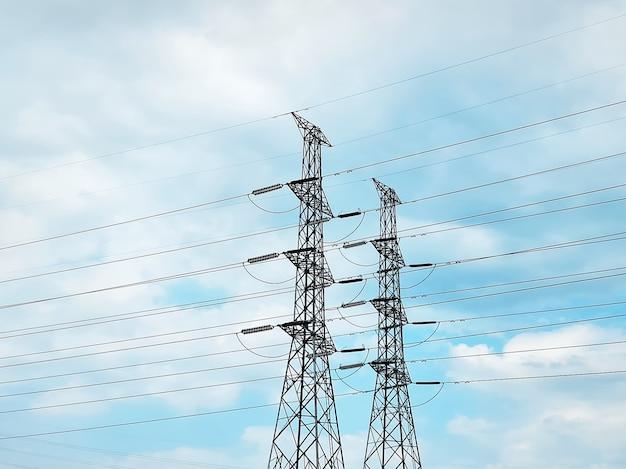 Torri di trasmissione di energia elettrica ad alta tensione contro il cielo nuvoloso blu