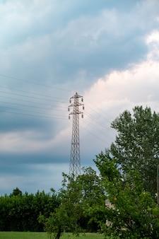 Linea ad alta tensione sullo sfondo del cielo e degli alberi