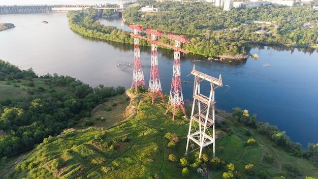 Pilastro ad alta tensione, linea elettrica aerea, background industriale. linee elettriche sul fiume