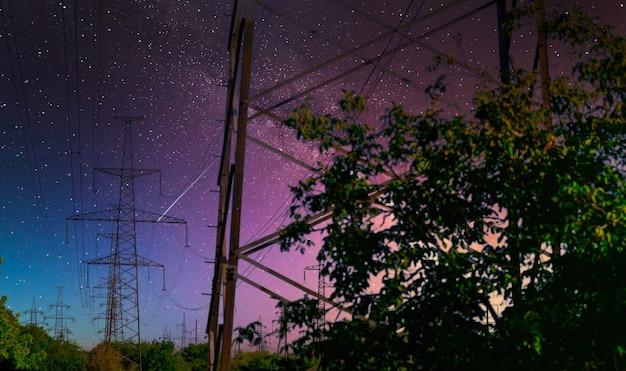 Polo ad alta tensione con la via lattea sul cielo. vista industriale delle linee ad alta tensione.