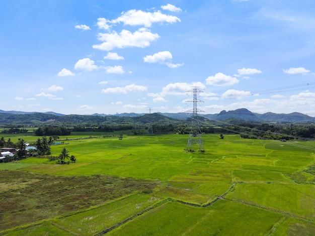 Posta ad alta tensione, sfondo del cielo della torre ad alta tensione sulla foresta di montagna, pali dell'elettricità e linee di trasmissione di energia elettrica contro la campagna con campo di riso verde