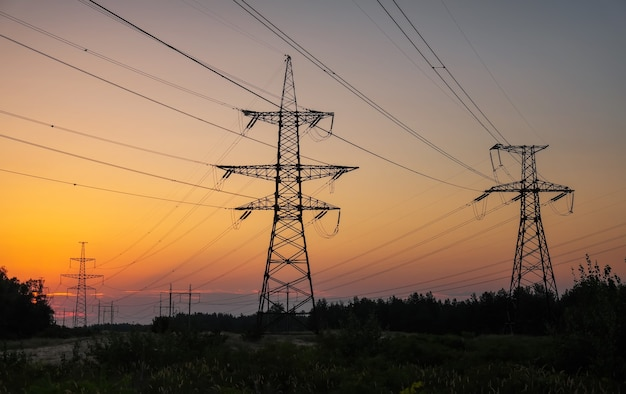 Linee elettriche ad alta tensione durante l'alba infuocata