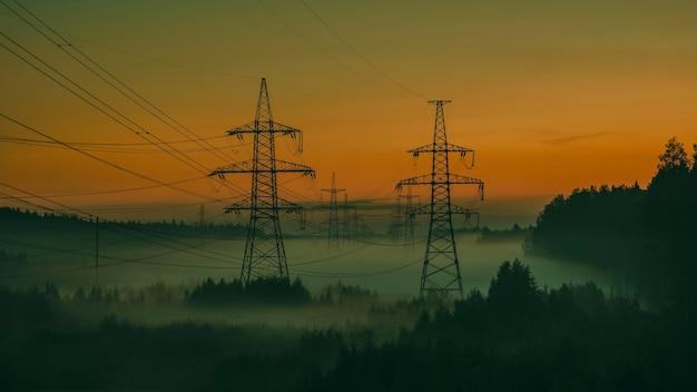 Poli di alimentazione ad alta tensione nella nebbia serale nel tramonto estivo