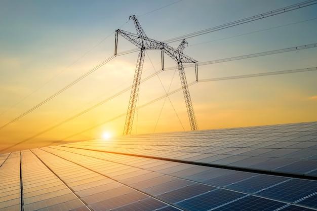 Tralicci ad alta tensione con linee elettriche che trasferiscono elettricità da vendite solari fotovoltaiche all'alba. produzione del concetto di energia sostenibile.
