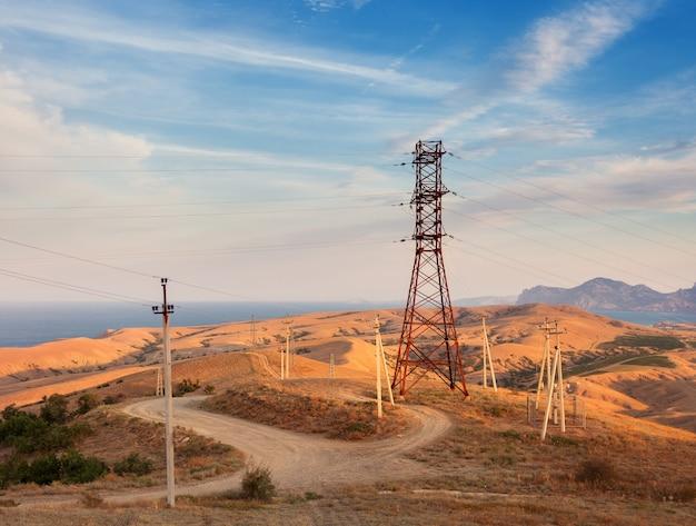 Torre ad alta tensione in montagna sullo sfondo del cielo colorato al tramonto.