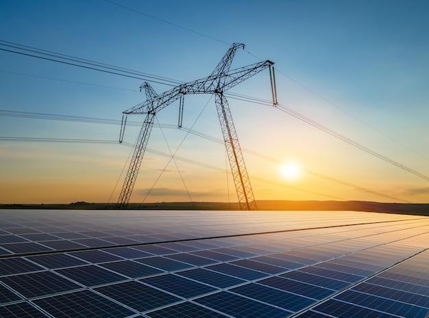 Torri ad alta tensione con linee elettriche che trasferiscono energia da pannelli solari fotovoltaici al tramonto. produzione del concetto di elettricità sostenibile.