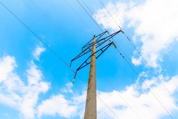 Linea di trasmissione ad alta tensione con supporti in calcestruzzo, cielo blu. sistema elettrico