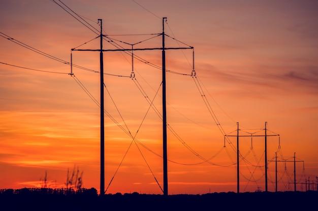 Cavi ad alta tensione al tramonto. una lunga fila di fili elettrici