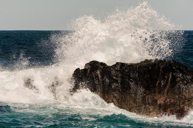 Alta onda di mare in tempesta che batte la roccia in acqua sotto il cielo limpido in giornata di sole
