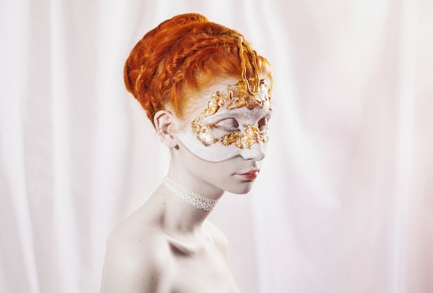 Acconciatura da sposa alta in stile greco. ritratto di stile di voga di una ragazza con un bodyart bianco rosso e dorato sul viso. progetto di pittura del corpo