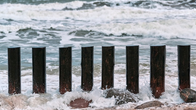 Alti frangiflutti in legno in onde blu del mare, vista ravvicinata. pali lunghi o pennelli in acqua