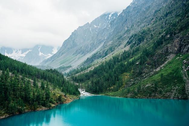 Il torrente dell'altopiano sfocia nel lago di montagna sullo sfondo del bellissimo grande ghiacciaio tra dense nuvole basse e foreste di conifere.