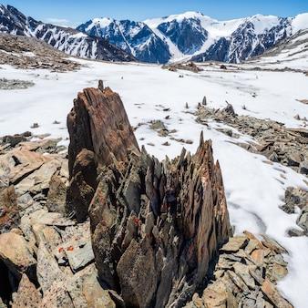 Paesaggio dell'altopiano con pietre affilate di forma insolita. fantastico paesaggio montano panoramico con grandi pietre appuntite incrinate in mezzo alla neve sotto il cielo blu alla luce del sole. rocce taglienti.