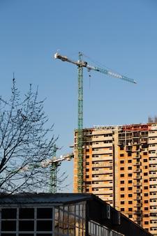 Grattacielo gru ed edifici residenziali sullo sfondo di un cielo blu