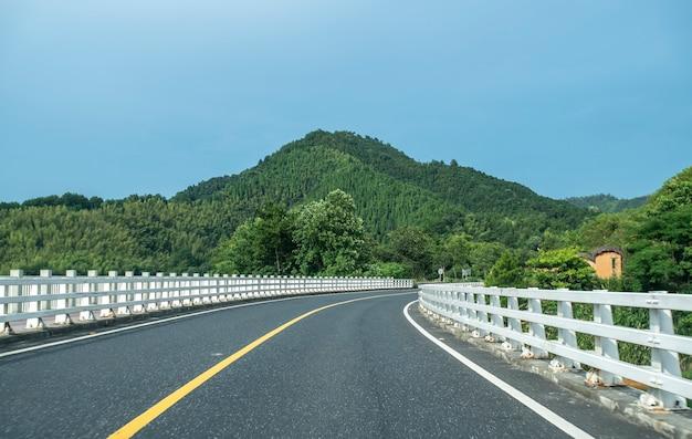 Autostrada e sfondo di montagna verde