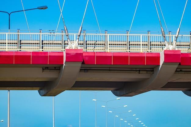 Svincolo autostradale con ponte e sole sullo sfondo.