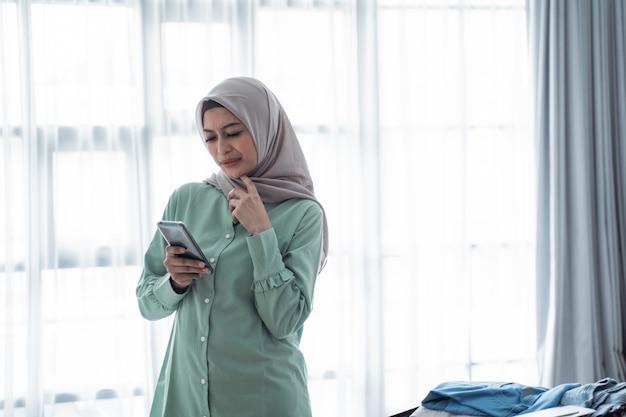 Donna hijab che controlla gli orari di partenza tramite l'app per smartphone