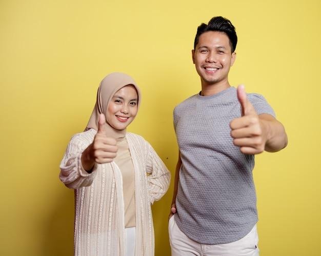 Hijab donna e uomo felici e mostrano il pollice insieme. isolato su uno sfondo giallo
