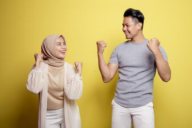 Hijab donna e uomo che sorridono a vicenda espressione molto eccitante isolato su uno sfondo giallo