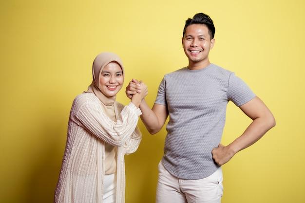 Hijab donna e uomo sorridente tenere la mano isolata su uno sfondo giallo