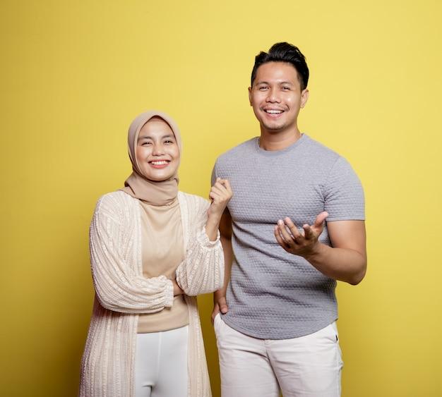 Hijab donna e uomo sorridente guardando la telecamera chiedendoti isolato su uno sfondo giallo