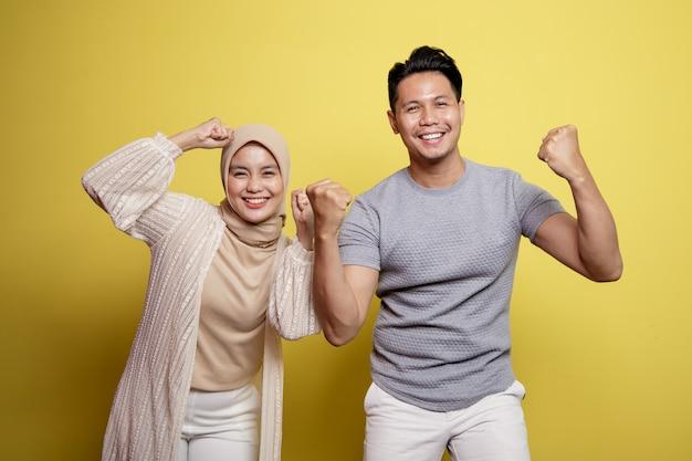 Hijab donna e uomo sorridente espressione molto eccitante isolato su uno sfondo giallo