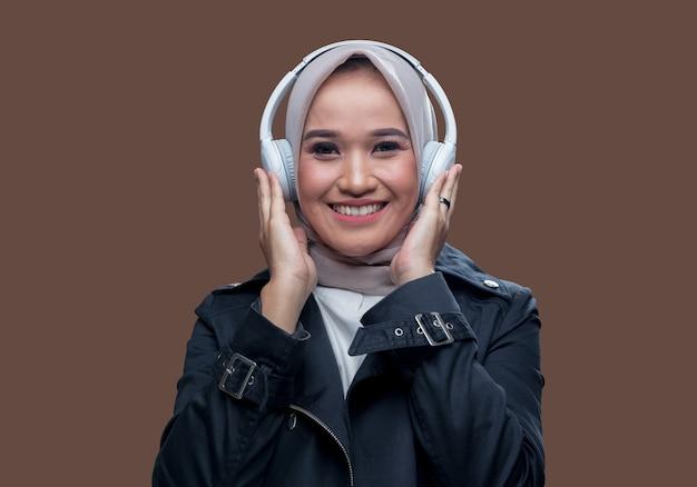 Hijab donna in posa indossando cuffie wireless con un sorriso