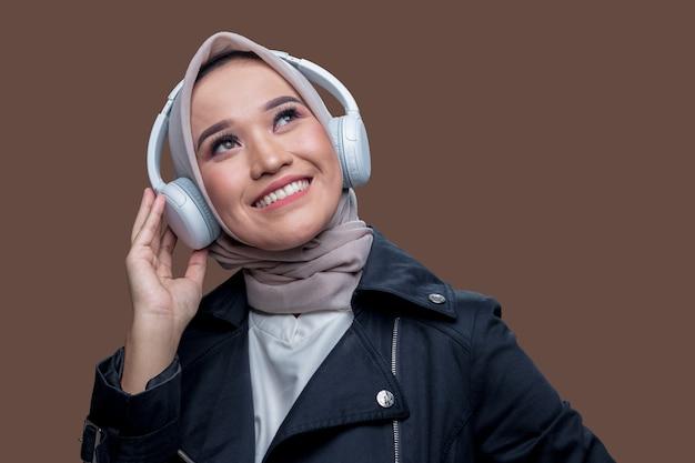 La donna hijab stava ascoltando musica usando le cuffie wireless con un'espressione sorridente mentre guardava in alto