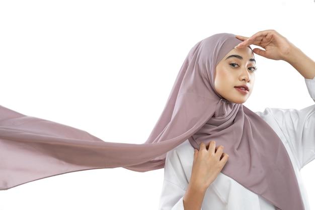 Hijab donna che indossa un velo viola che fluttua nel vento con gesti delle mani sulla fronte