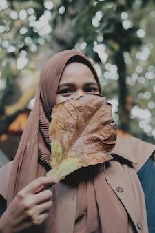 Hijabwoman che tiene una grande foglia che gli copre il viso